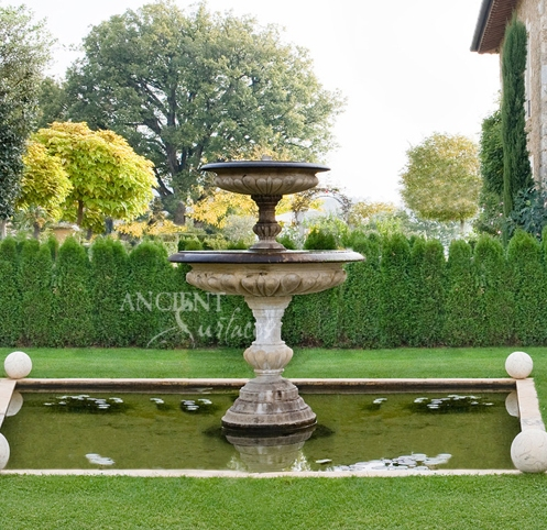 'Foundation Slabs' on the Pool Coping Edge. Antique tiered stone fountain by Ancient Surfaces. Photo of a hotel exterior garden with lawn.