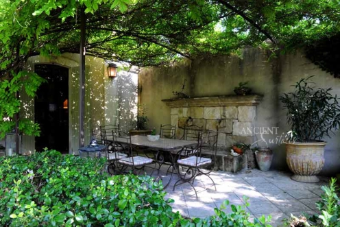 Outdoor Courtyard with heavy foliage, a wall fountain and an outdoor dining table by Ancient Surfaces.