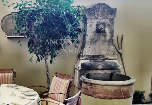 Small Antique French Limestone Wall Fountain installed in a small courtyard. By Ancient Surfaces.