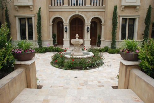 A hand carved entryway courtyard stone fountain sitting on top of reclaimed Arcane Stone flooring. By Ancient Surfaces